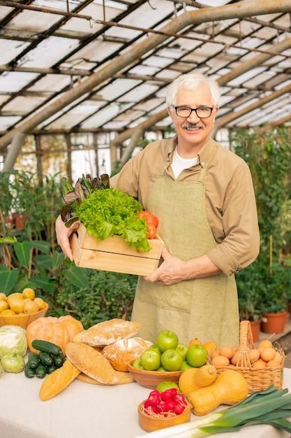 Retrato de um fazendeiro sênior sorridente com bigode segurando uma caixa de legumes frescos em estufa Foto Premium