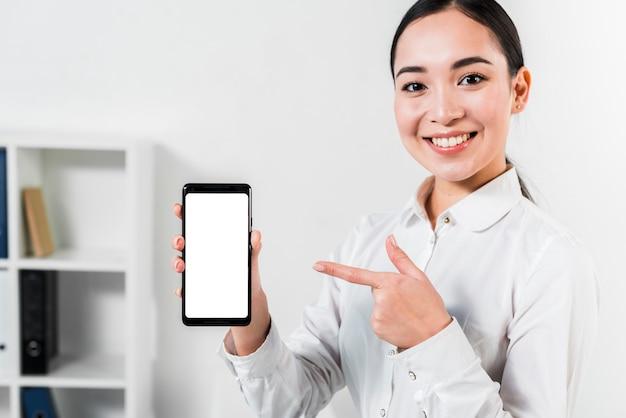 Retrato, de, um, feliz, asiático, jovem, executiva, apontar telefone móvel Foto gratuita
