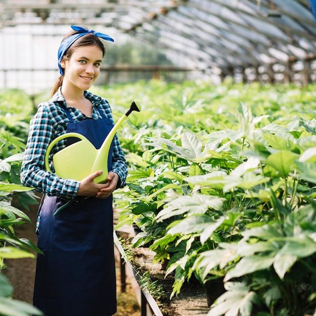 Retrato, de, um, feliz, femininas, jardineiro, segurando, lata molhando, em, estufa Foto gratuita