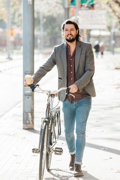Retrato, de, um, feliz, homem jovem, andar, com, bicicleta, ligado, rua cidade Foto gratuita