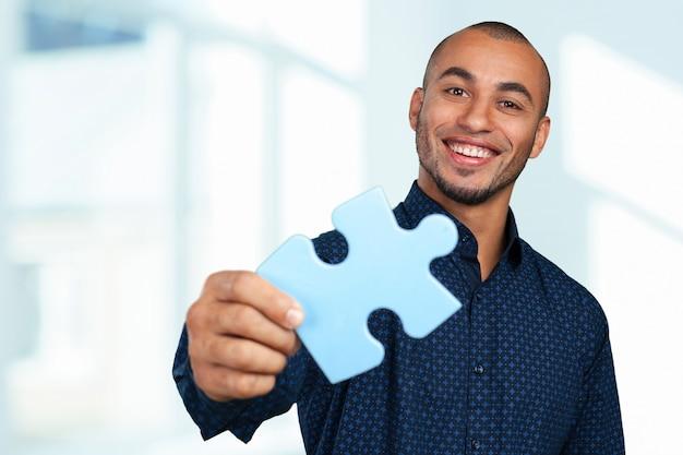 Retrato, de, um, feliz, jovem, homem negócios, segurando, quebra-cabeça Foto Premium