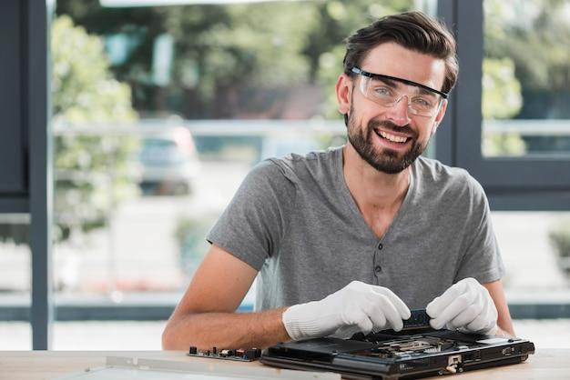 Retrato, de, um, feliz, jovem, macho, técnico, reparar, computador Foto gratuita