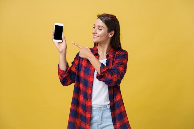 Retrato, de, um, feliz, menina jovem, vestido, em, verão, apontar dedo, em, tela vazia Foto Premium