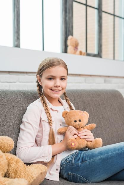 Retrato, de, um, feliz, menina, sentando, ligado, cinzento, sofá, segurando, urso teddy, olhando câmera Foto gratuita