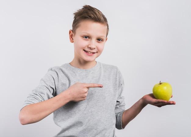 Retrato, de, um, feliz, menino, apontar, seu, dedo, direção, inteiro, maçã verde, em, mão Foto gratuita
