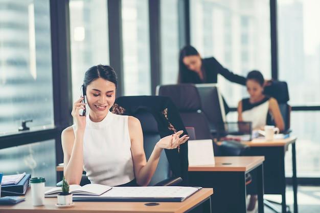 Retrato, de, um, feliz, mulher negócio, sentando, em, dela, local trabalho, em, escritório Foto Premium