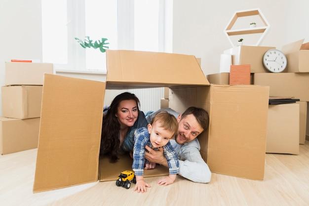 Retrato, de, um, feliz, pais, tocando, com, toddler, menino, dentro, a caixa papelão Foto gratuita