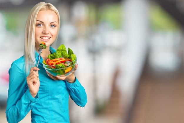 Retrato, de, um, feliz, playful, menina, comer, salada fresca, de, um, tigela Foto Premium