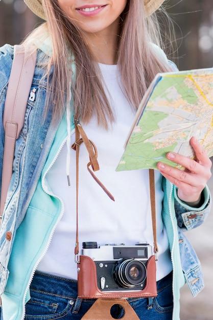 Retrato, de, um, femininas, viajante, segurando, vindima, câmera, e, mapa Foto gratuita