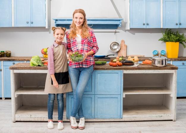 Retrato, de, um, filha sorridente, ficar, com, dela, mãe segura, tigela salada Foto gratuita