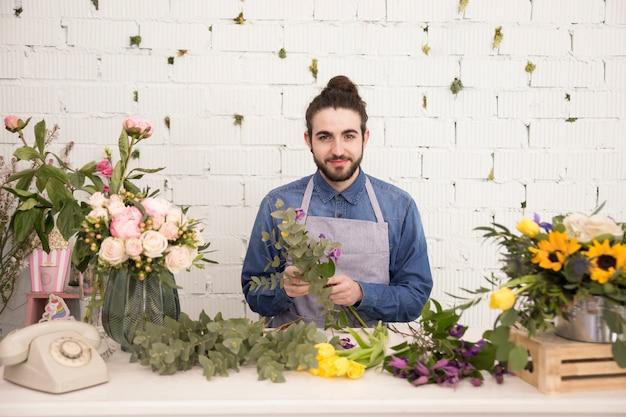 Retrato, de, um, florista macho, fazendo, a, flor, buquet, ficar, contra, parede branca Foto gratuita