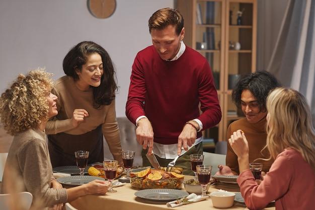 Retrato de um homem adulto sorridente cortando um delicioso peru assado enquanto desfruta do jantar de ação de graças com amigos e familiares. Foto Premium