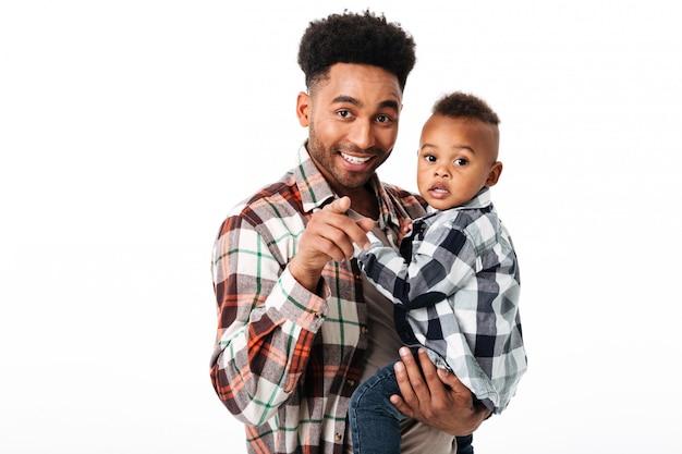 Retrato de um homem africano sorridente segurando seu filho pequeno Foto gratuita