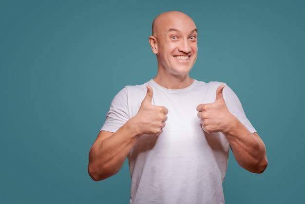 Retrato de um homem alegre, mostrando o gesto bem isolado sobre o fundo azul Foto Premium