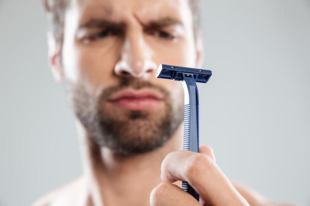 Retrato de um homem barbudo concentrado duvidoso olhando para navalha Foto gratuita
