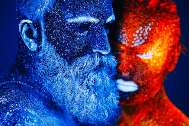 Retrato de um homem barbudo e uma mulher pintados em pó ultravioleta. Foto Premium
