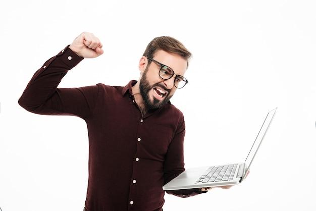Retrato de um homem barbudo feliz segurando o computador portátil Foto gratuita
