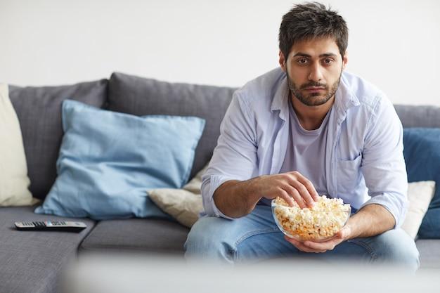 Retrato de um homem barbudo triste assistindo tv e segurando uma tigela de pipoca enquanto está sentado no sofá em casa Foto Premium