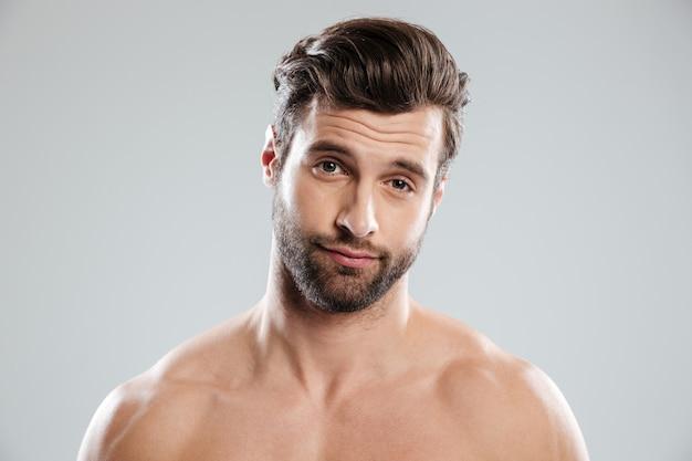 Retrato de um homem bonito e duvidoso com ombros nus Foto gratuita