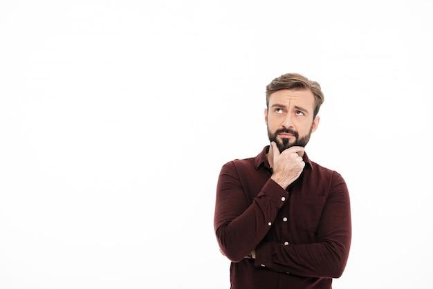 Retrato de um homem bonito pensativo olhando para longe Foto gratuita