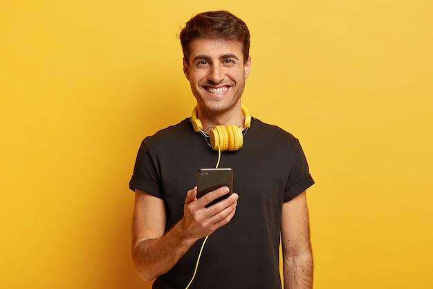 Retrato de um homem branco feliz com som e qualidade fantásticos de fones de ouvido, segurando um celular moderno Foto gratuita