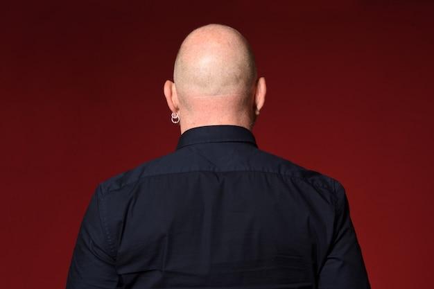 Retrato de um homem careca, retrovisor, sobre fundo vermelho Foto Premium