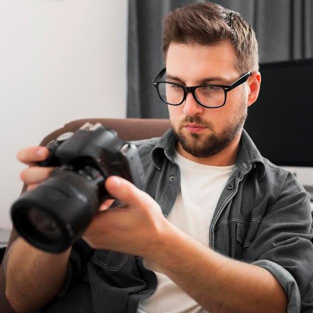 Retrato de um homem casual conferindo uma câmera profissional Foto gratuita