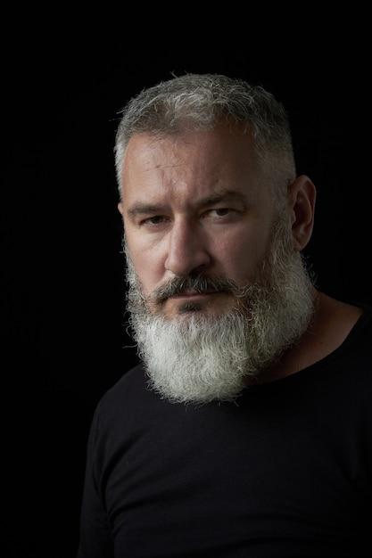 Retrato de um homem de cabelos cinza brutal com uma barba exuberante cinza e rosto estrito sobre um fundo preto, foco seletivo Foto Premium