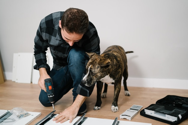 Retrato de um homem e seu cachorro montando móveis. faça você mesmo a montagem dos móveis. Foto Premium