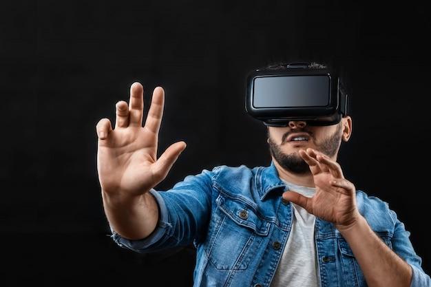 Retrato de um homem em óculos de realidade virtual, vr, contra um fundo escuro. Foto Premium