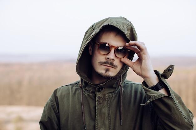 Retrato de um homem estiloso com bigode e barba em óculos de sol nas montanhas Foto Premium