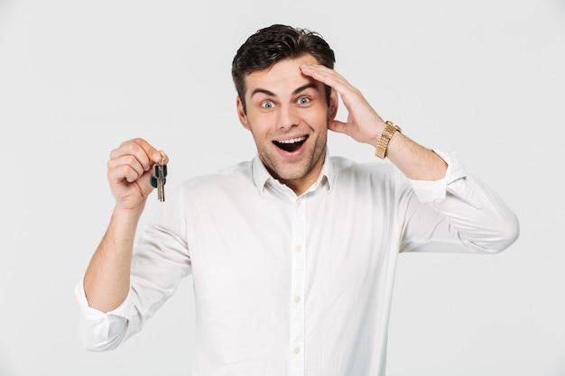 Retrato de um homem feliz animado, segurando as chaves Foto gratuita