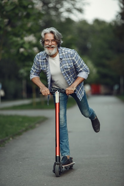 Retrato de um homem idoso com patinete em um parque de verão Foto gratuita