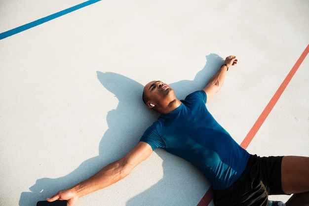 Retrato de um homem jovem cansado africano fitness em fones de ouvido Foto gratuita