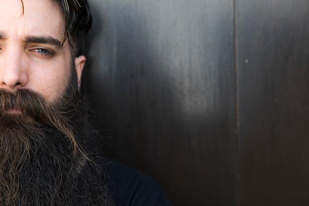 Retrato, de, um, homem jovem, com, longo, barba, olhando câmera Foto gratuita