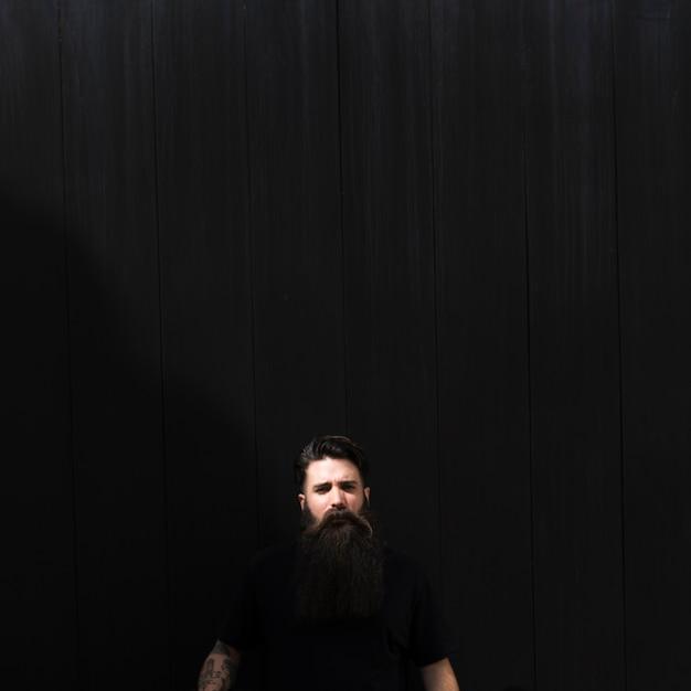 Retrato, de, um, homem jovem, contra, experiência preta Foto gratuita