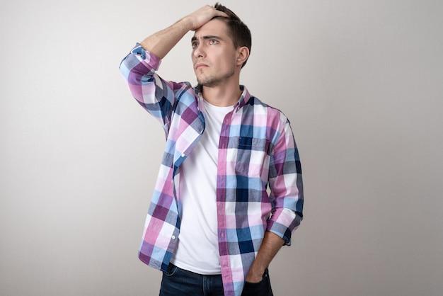 Retrato, de, um, homem jovem, em, um, camisa xadrez, triste, olhar Foto Premium