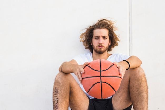 Retrato, de, um, homem jovem, sentando, com, basquetebol Foto gratuita