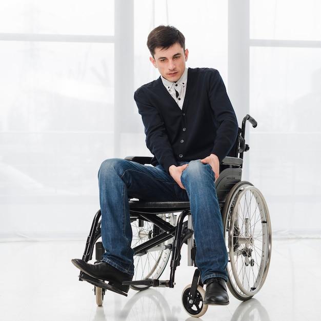 Retrato, de, um, homem jovem, sentando, ligado, cadeira rodas, tendo, dor, em, seu, perna Foto gratuita