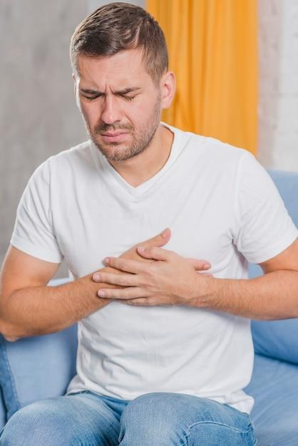 Retrato, de, um, homem jovem, sentar sofá, tendo, peito dor Foto gratuita