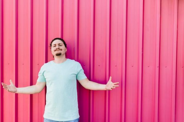 Retrato, de, um, homem jovem, shrugging, contra, ondulado, folha metal Foto gratuita