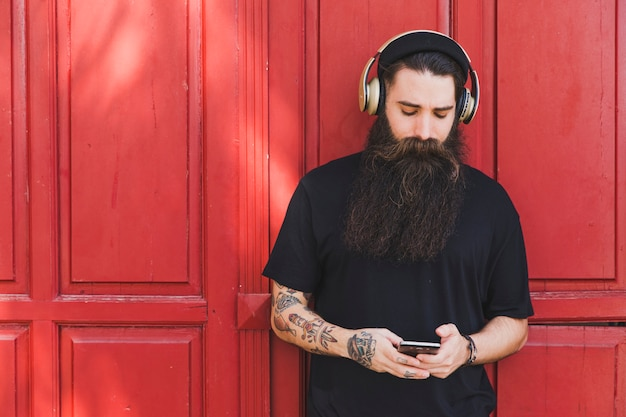 Retrato, de, um, homem jovem, usando, telefone móvel, com, auscultadores, ligado, seu, encabece pé, contra, parede vermelha Foto gratuita