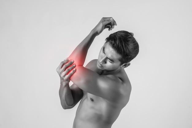 Retrato de um homem muscular com dor no cotovelo isolado no fundo branco Foto gratuita