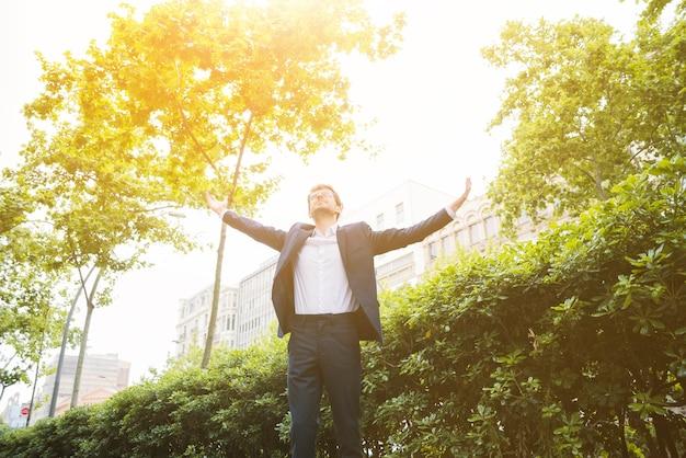 Retrato, de, um, homem negócios fica, frente, predios, levantando, seu, braços Foto gratuita