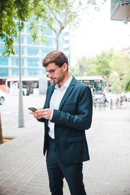 Retrato, de, um, homem negócios fica, ligado, rua, usando, telefone móvel Foto gratuita