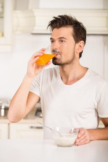 Retrato de um homem novo que esteja bebendo o suco na cozinha. Foto Premium