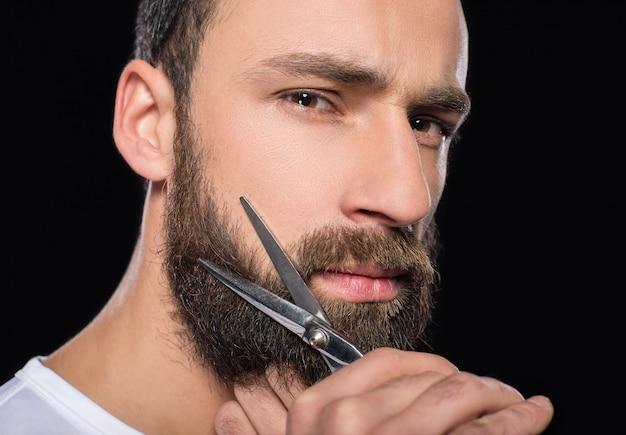 Retrato de um homem que corta sua barba com tesouras. Foto Premium