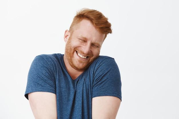 Retrato de um homem ruivo fofo, satisfeito e feliz, feliz e engraçado, de camiseta azul, encolhendo os ombros e apoiando o rosto no ombro enquanto sorri amplamente, corando de alegria e felicidade Foto gratuita