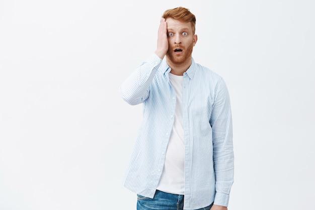 Retrato de um homem ruivo maduro e arrasado e atordoado em uma camisa, segurando a palma da mão no rosto e deixando cair o queixo de tremer Foto gratuita