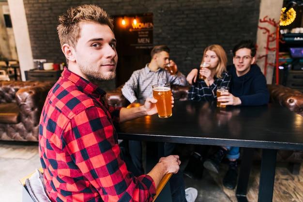 Retrato, de, um, homem, segurando, a, vidro cerveja, sentando, com, amigos, olhando câmera Foto gratuita
